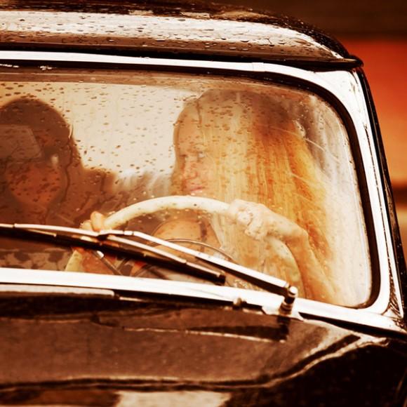 Two young women driving retro car.